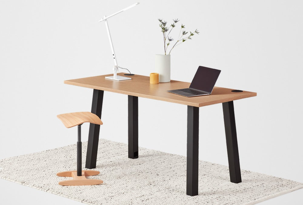 Boden Seated Fixed Height Desk Laminate oak top with black frame. Tic toc in natural and Beam LED desk lamp.