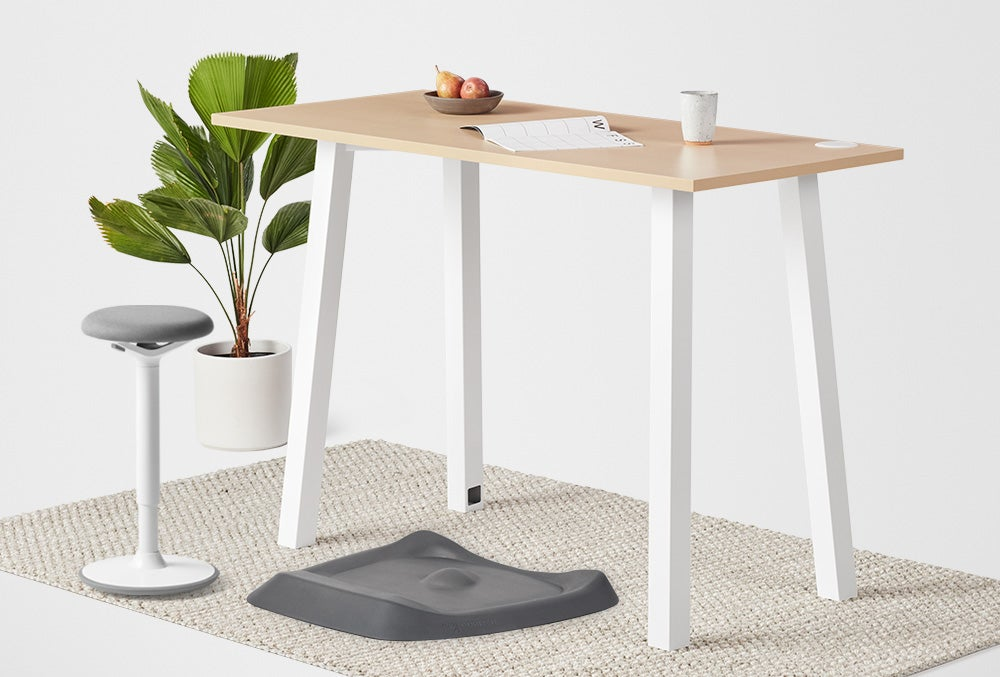 Boden Standing Fixed Height Desk maple laminate top with white frame. Luna with white base and grey upholstery and Topo anti-fatigue mat in grey.