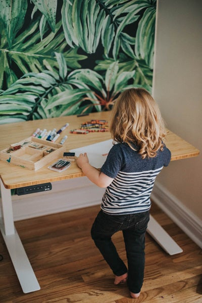 Kid standing and drawing at a Jarvis Kids adjustable height standing desk