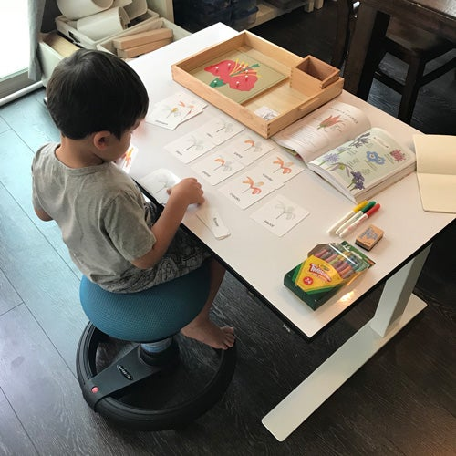 A kid learns and plays at his standing desk