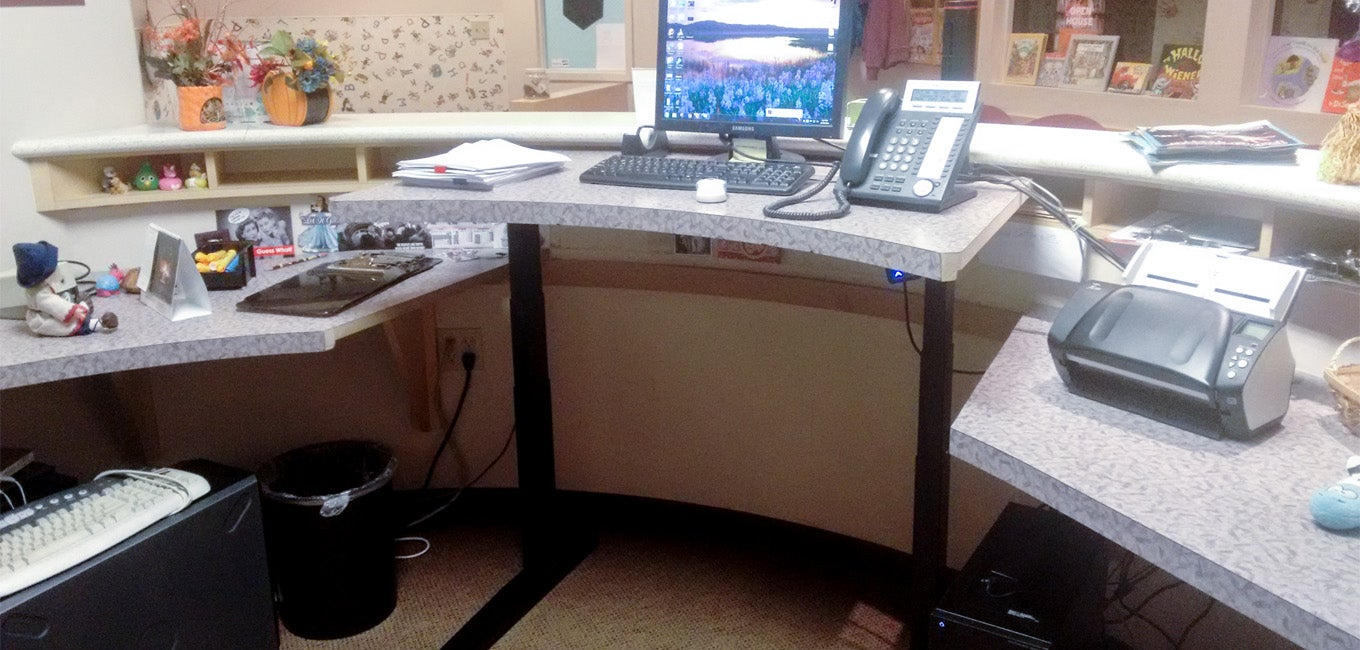 A jarvis standing desk with a customized desktop to match surrounding table