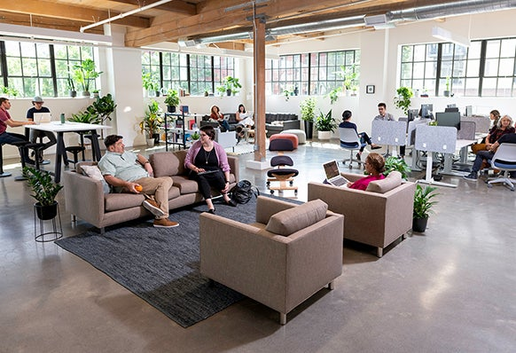 """Image of co-workers in an open office. Link to """"everyone hates the open office"""" article."""