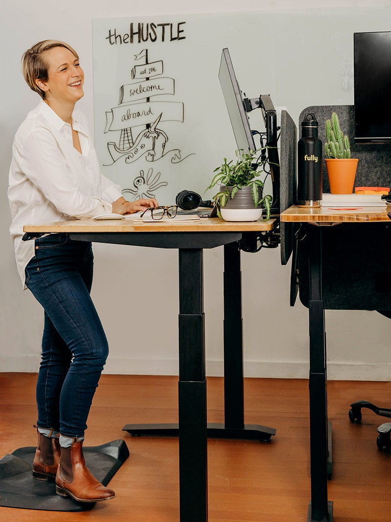Woman standing at a Jarvis desk laughing