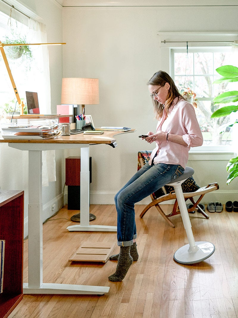 Woman sitting on a Luna Stool with Jarvis Bamboo Standing Desk