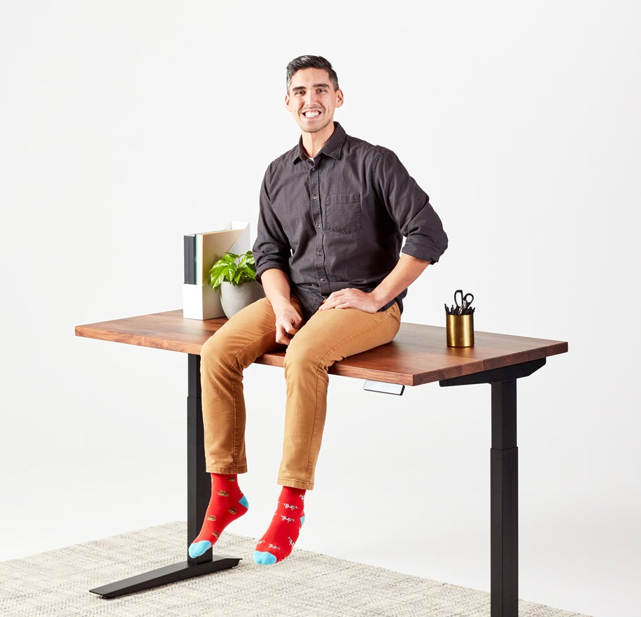 man sitting on jarvis adjustable standing desk smiling
