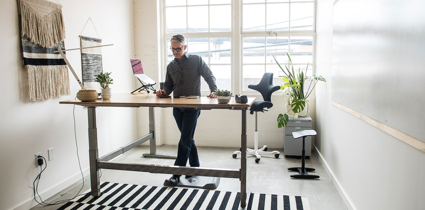 Man working in office on a Jarvis Standing Desk