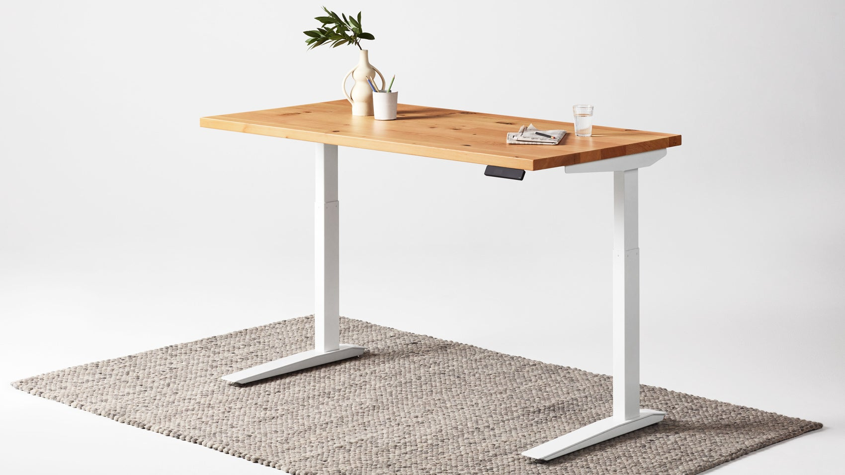 Fully Jarvis Standing desk with hardwood top on a rug against a white backdrop