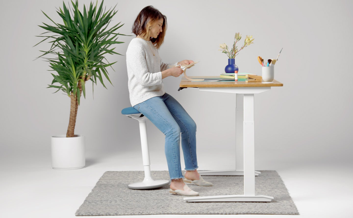 fully luna standing desk stool blue with white base in use by woman
