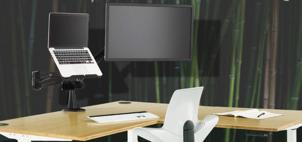 A Fully Jarvis desk with a monitor arm and laptop tray against bamboo background