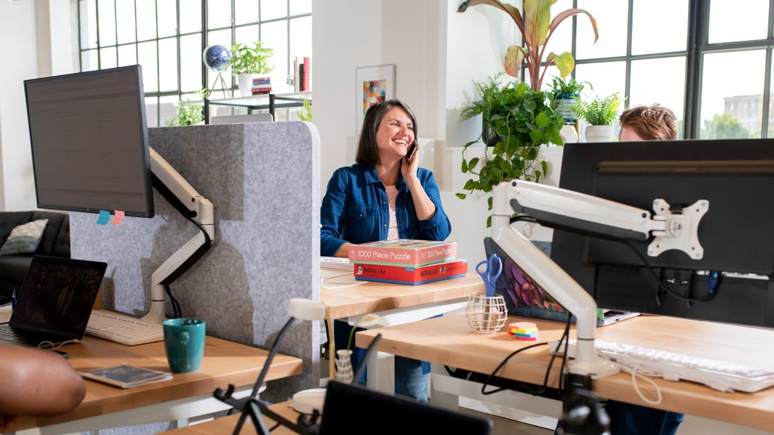 A Fully customer service representative on the phone at a Jarvis standing desk pod
