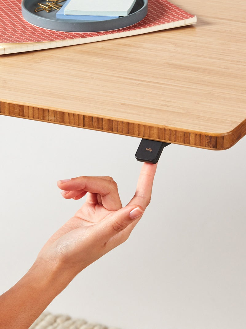 Finger pushing on the Jarvis Bamboo Up/Down toggle on the Jarvis standing desk