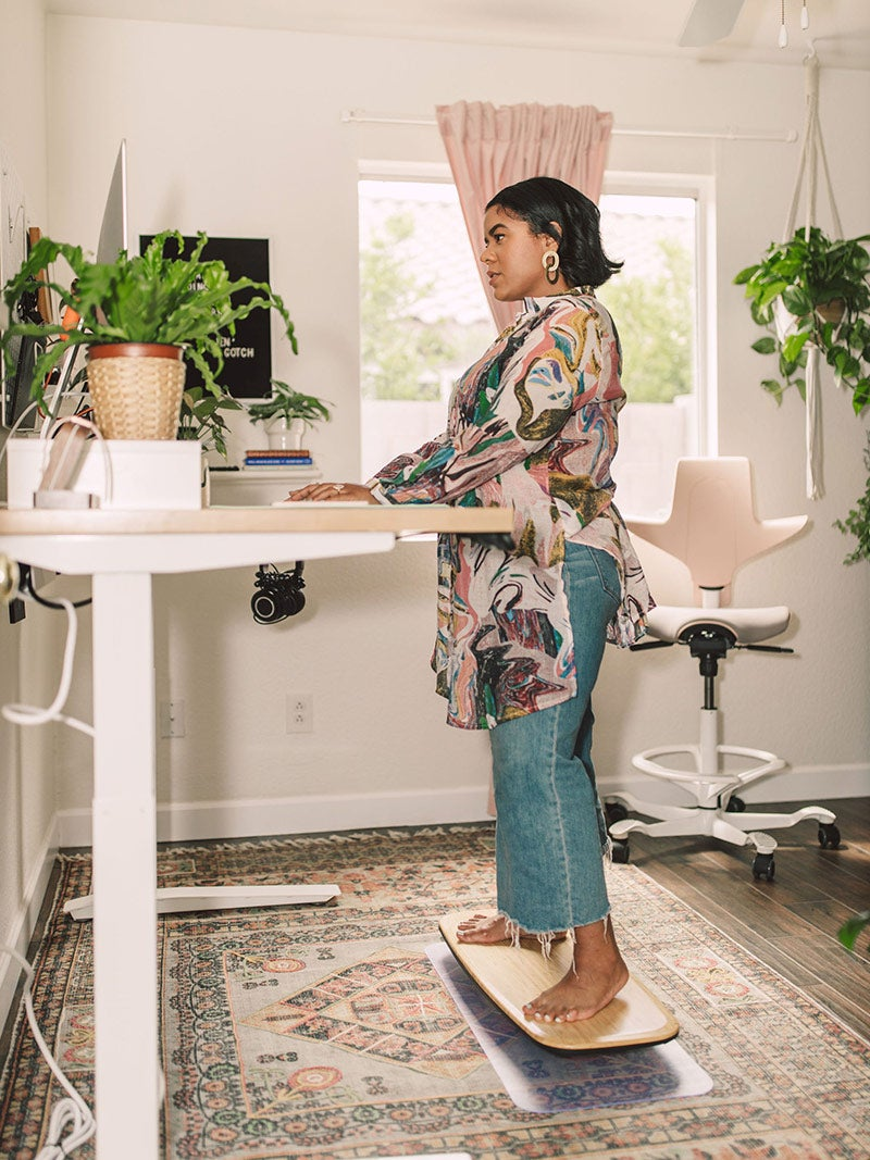Woman working at a standing desk while balancing on Floatdeck