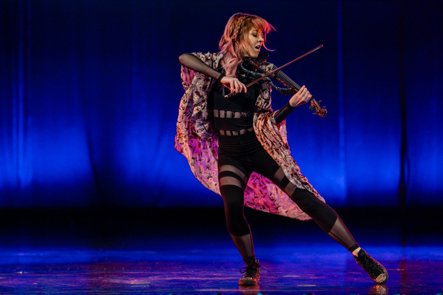 Lindsey Stirling on stage at Summit of Greatness performing the violin