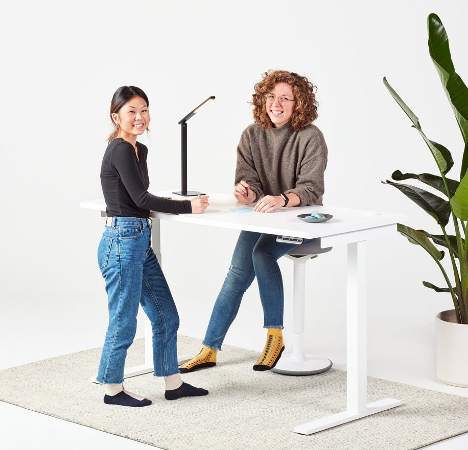 fully remi standing desk with aleris desk lamp and luna stool and two women smiling