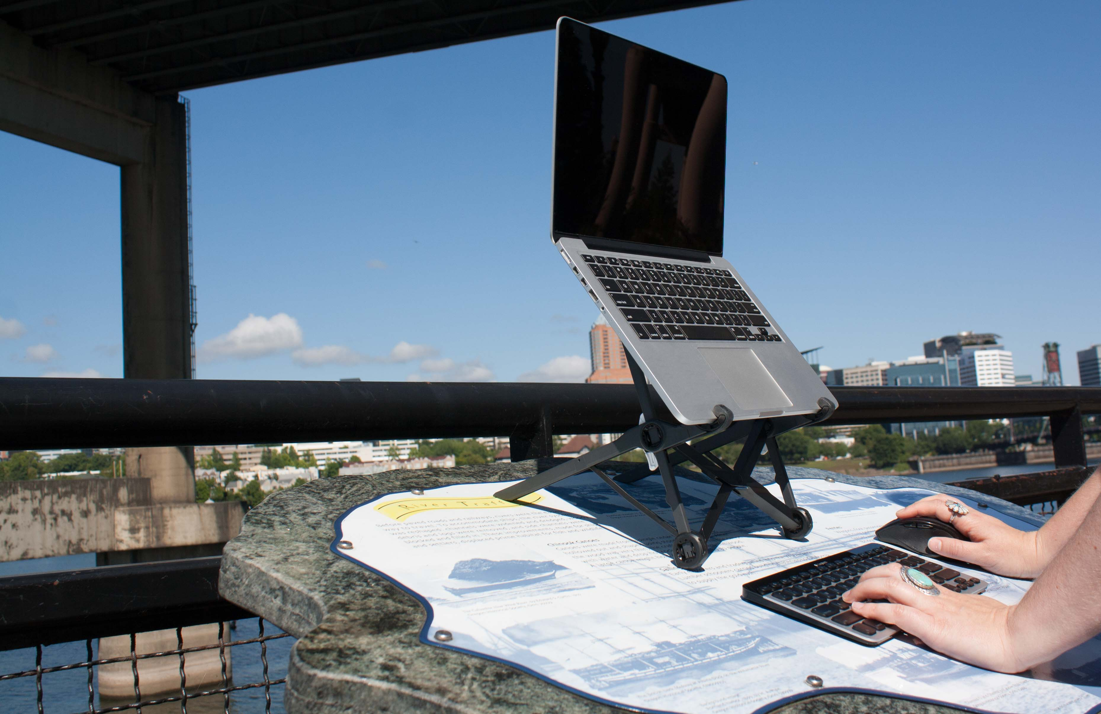 A hand works on a laptop on a roost outside