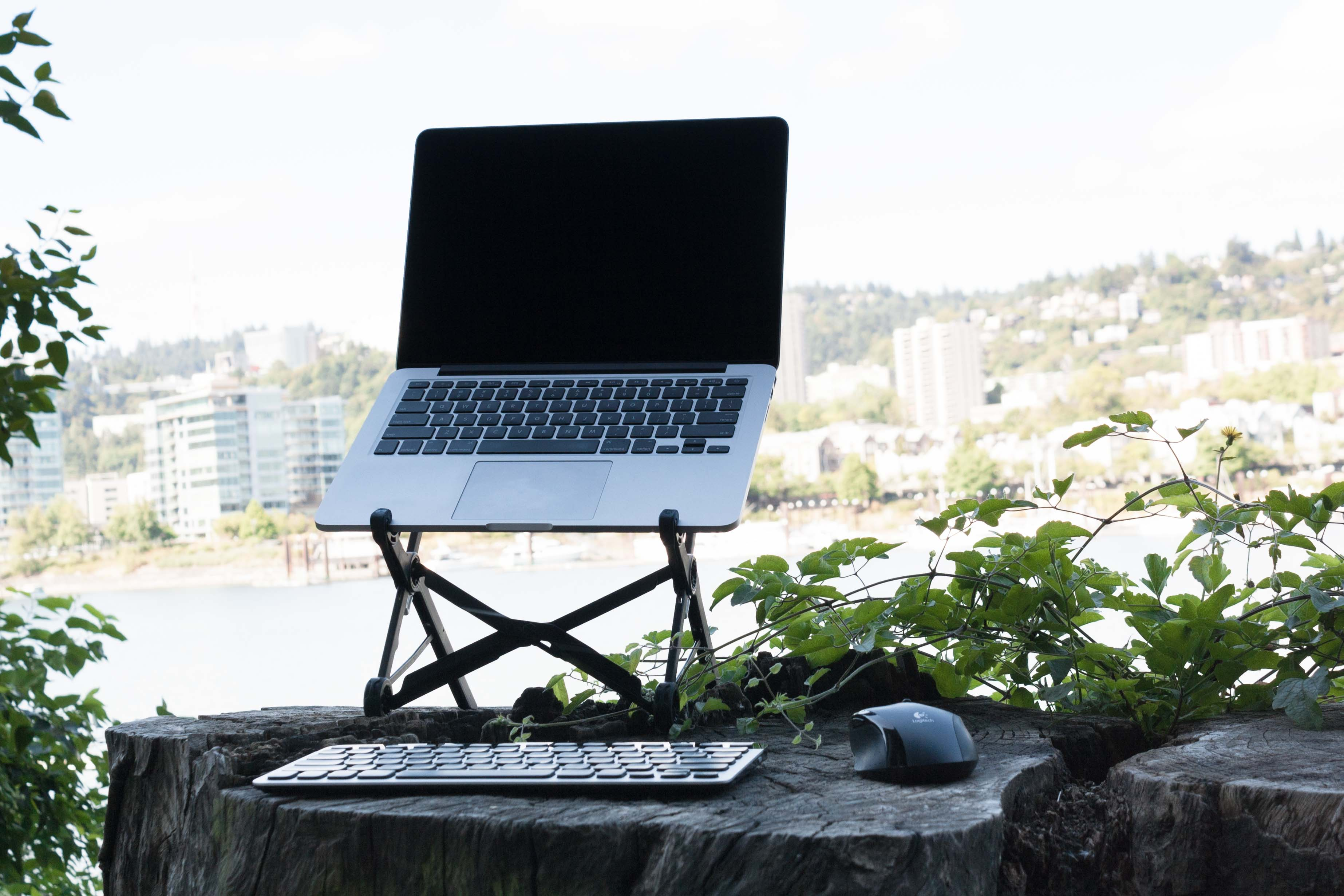 Laptop in a Fully Roost with keyboard and mouse on tree stump beside river