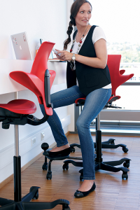 Woman sitting on red Capisco saddle seat chair