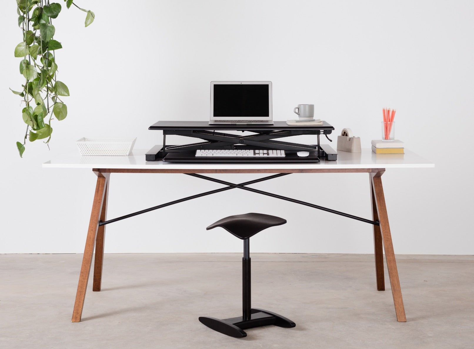 Fully cooper standing desk converter in black on a table with a black Tic Toc chair