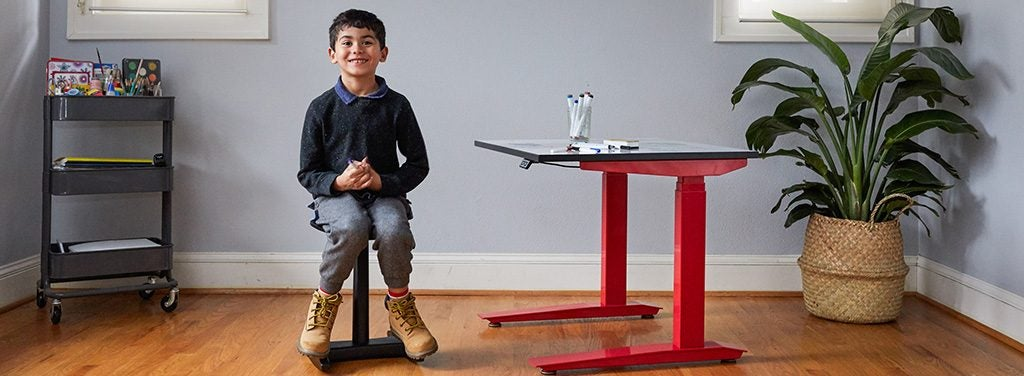 Kid sitting on Tic Toc Tyke with Jarvis kids standing desk