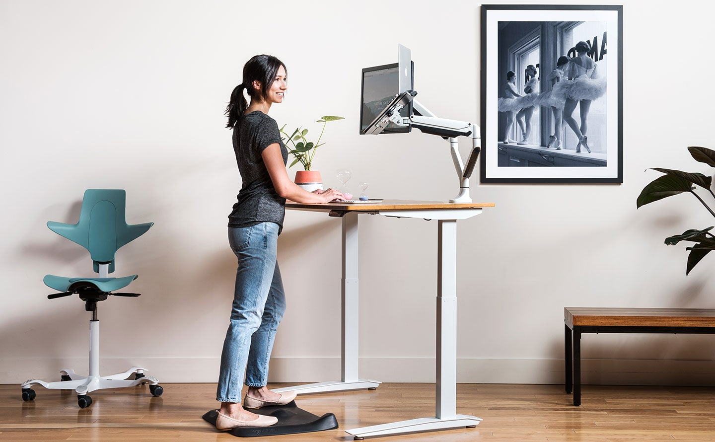 fully topo mini and topo anti fatigue mats topo mini in use by woman with jarvis desk lifestyle photo
