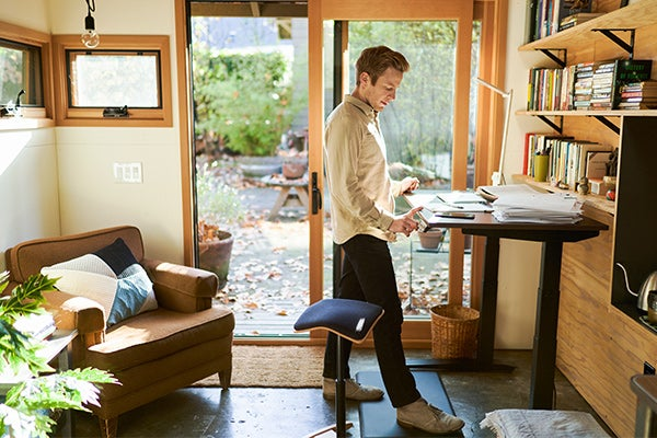 man working from home office with fully jarvis standing desk and tic toc chair
