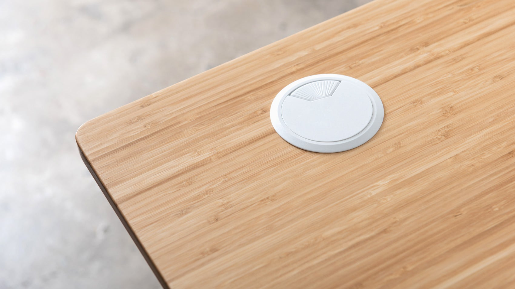 A close up of a white grommet cover for Jarvis Bamboo standing desk